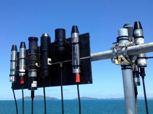 Figure 2: Irradiance radiometers lined up, with a view of Pelorus and Orpheus Islands in the background. 4 x Ramses, 2 x HyperOCR, 1 x USSIMO, and 1 x MS8 sensors are visible. Photo by M. Slivkoff.